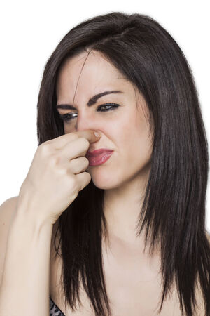 Beautiful upset girl smelling stench photo