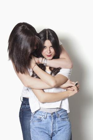 Mooie zusters lachend en knuffelen