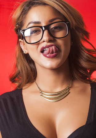 Sexy beautiful woman wearing glasses and licking her lips on red background photo
