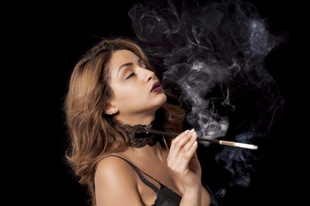 Beautiful sexy woman with cigarette holder smoking photo