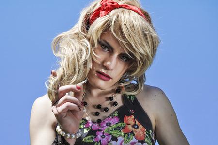 Mooie drag queen dragen van een blonde pruik en op zoek