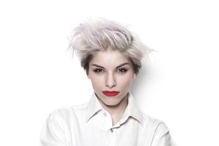 Beautiful girl with dyed hair being serious and wearing a white shirt photo