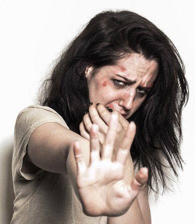 beaten up: Sad beaten up girl with wounds on the face being scared and asking to stop