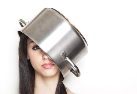 annoyed girl: Beautiful annoyed girl using a steel pot like a hat