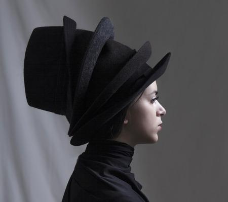 Mooi meisje dragen meerdere hoeden profiel