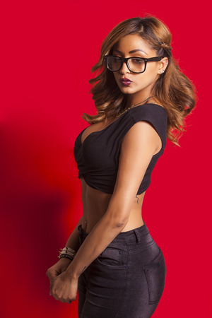 Beautiful sexy woman wearing glasses and posing on red background Stockfoto