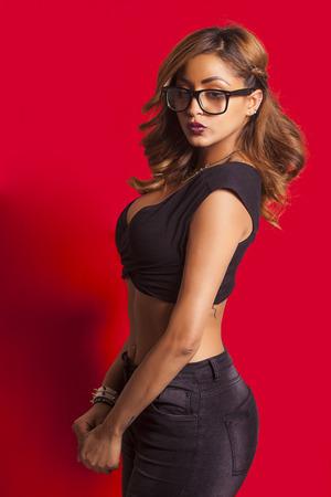 Mooie sexy vrouw draagt een bril en poseren op rode achtergrond