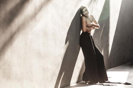 Mooie vrouw die zich door de muur in de zon en op zoek Stockfoto