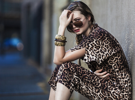 Beautiful and weak woman sitting in the city and wearing a leopard-skin dress Stockfoto