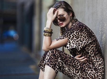 Mooi en zwakke vrouw in de stad en het dragen van een luipaard-huid jurk