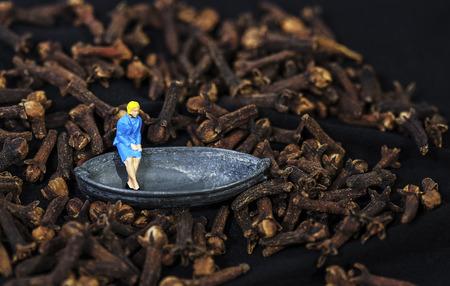 Tiny Toy vrouw zitten in een boot drijvend in een teentje zee