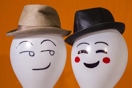 Witte ballon personages dragen van hoeden en lachen naar elkaar Stockfoto