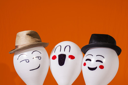 White balloon characters wearing hats and making faces