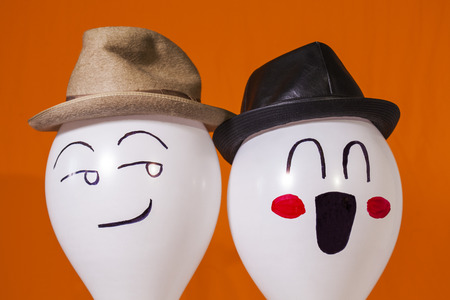 White balloon characters making faces and wearing hats