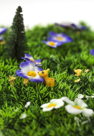 Tiny Toy giraffe ruiken een kunstmatige bloem in een plastic tuin