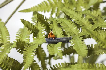 Tiny speelgoed man zit in een boot op een boom Stockfoto