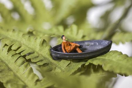 Tiny speelgoed man zit in een boot