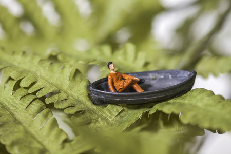 Tiny toy man sitting in a boat