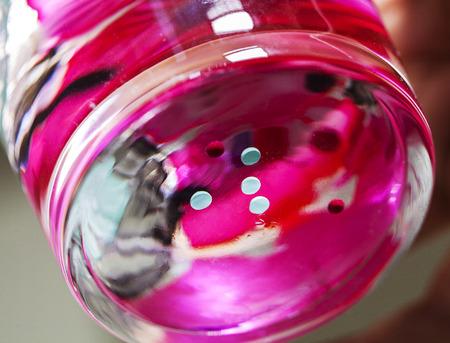 Crazy kleurrijke nagellak effect in een glas water Stockfoto
