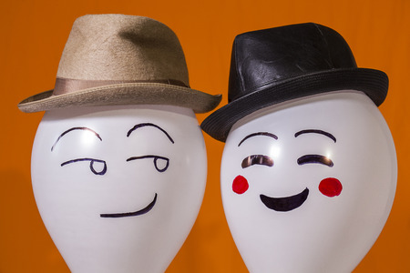 White balloon characters wearing hats and smiling at each other Stockfoto