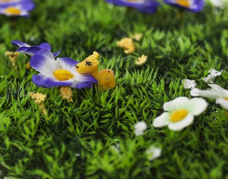 Tiny Toy giraffe ruiken een kunstmatige bloem