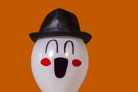 Smiling white balloon wearing a black hat