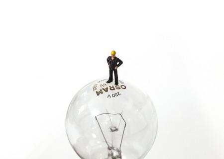 Tiny toy man standing on a light bulb Stockfoto