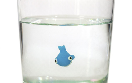 Tiny toy whale smimming in a glass of water