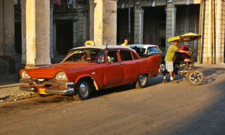 American taxi car parked on the street in Havana, Cuba  A man with bici taxi walking behind