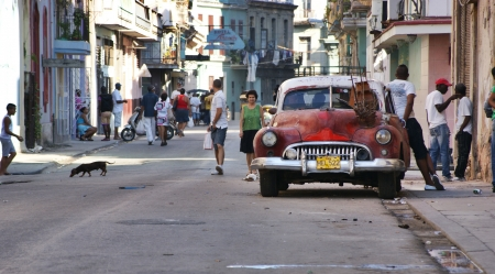 habana: Central Havana, Street scene with old american car parked on the side with wooden boat on it, few people standing beside