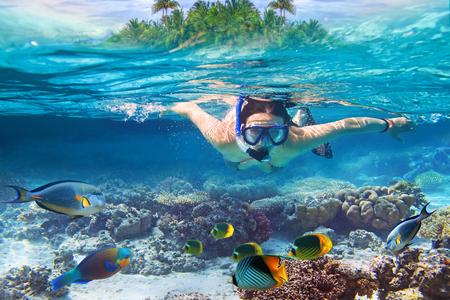 熱帯水でシュノーケ リングで若い女性