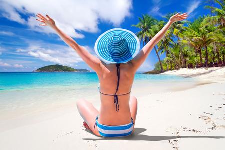 Frau im Hut genießen Sonne Urlaub auf dem tropischen Strand