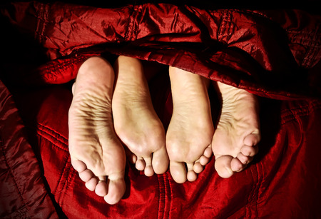 Closeup of couples feet under blanket