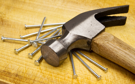 pounding head: Hammer and nails on wooden board Stock Photo