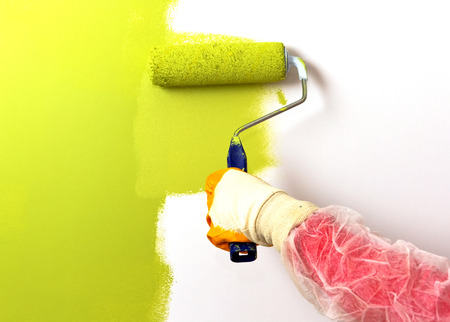 paint wall: Wall painting in green colour with rollers Stock Photo