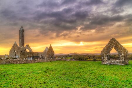 ancient ireland celtic cross: Kilmacduagh monastery at sunset, Ireland Stock Photo