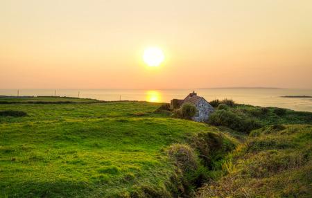 doolin: Irish cottage house near ocean at sunset