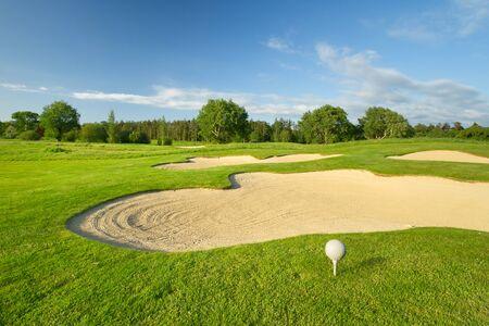 Golf ball on the beautiful golf course with sandbanks