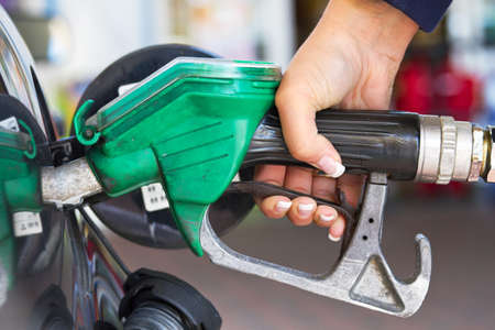 refilling: Female hand refilling the car with fuel