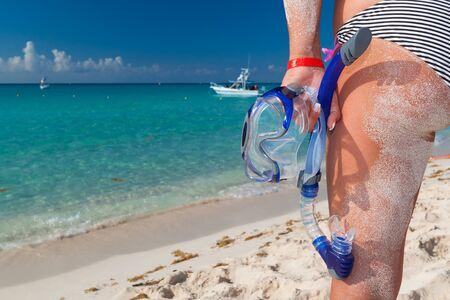 Woman in bikini with snorkeling mask standing on Caribbean beach