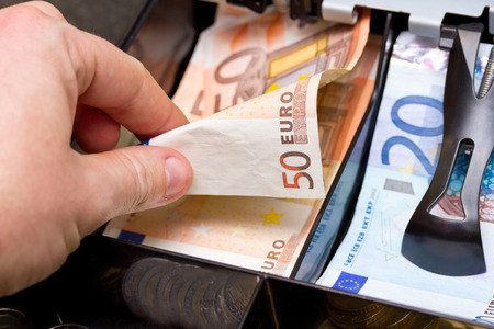 cash in hand: Hand taking change in euro from the till Stock Photo