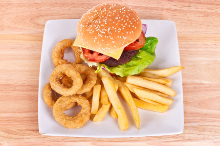 french fries plate: Cheeseburger with chips and onion rings on the plate