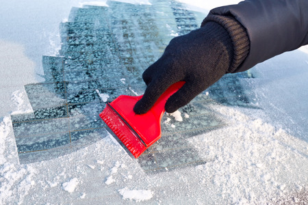 Scraping ice from the car window