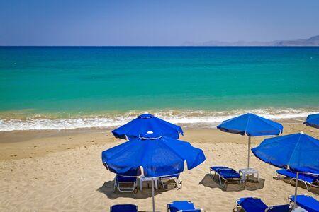 parasols: Blue parasols and deckchairs at Aegean Sea of Greece Stock Photo