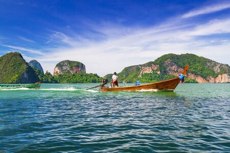 navigating: Man navigating his boat to transport tourist over the Phang Nga National Park, Thailand