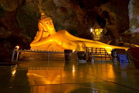 eyes cave: Golden statue of reclining buddha in Suwancoha cave temple in Phangnga, Thailand