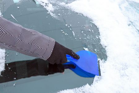 Hand scraping ice from the car window during winter time