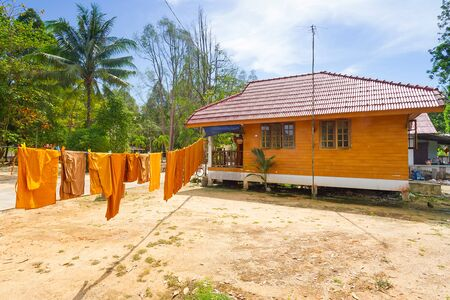 koh kho khao: Orange monk clothes drying under the sun in Thailand