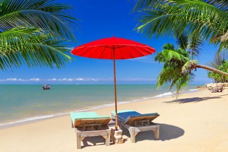 Tropical beach scenery with red parasol and deckchairs in Thailand Stock Photo
