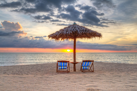 koh kho khao: Tropical beach scenery with parasol and deckchairs at sunset in Thailand Stock Photo